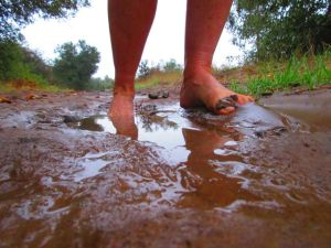 bare feet in mud puddle